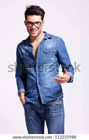 young casual man wearing glasses welcoming you, on gray background
