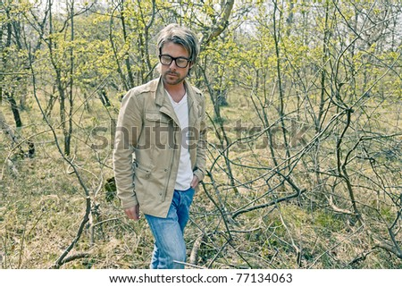 Young casual man with glasses walking in nature.