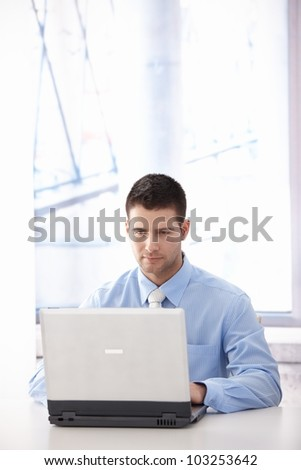 Young casual office worker working on laptop in bright office.