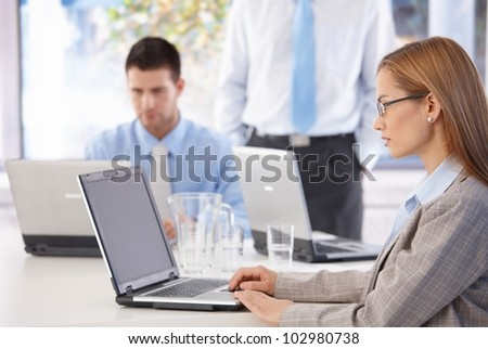 Young casual office workers working on laptop in bright office. - stock photo