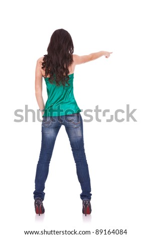 young casual woman points finger at something in her back. Isolated on white background