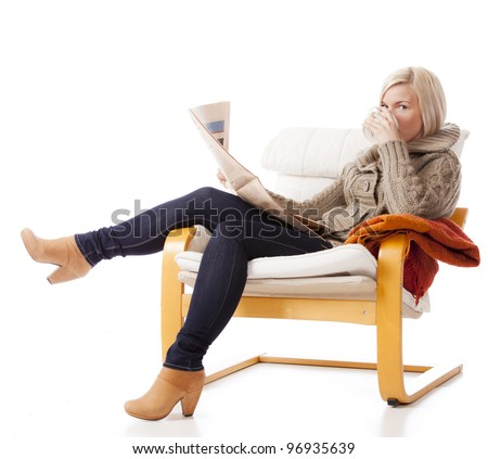 young, casual woman sitting in an armchair reading a newspaper. She is looking in to camera drinking from a cup of coffee or tea.