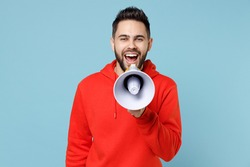 Young caucasian attractive happy bearded handsome leader man 20s wearing casual red orange hoodie screaming hot news shouting in megaphone loudly isolated on blue color background studio portrait.