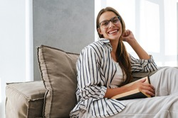 Young caucasian attractive woman smiling and reading book while sitting on sofa at home