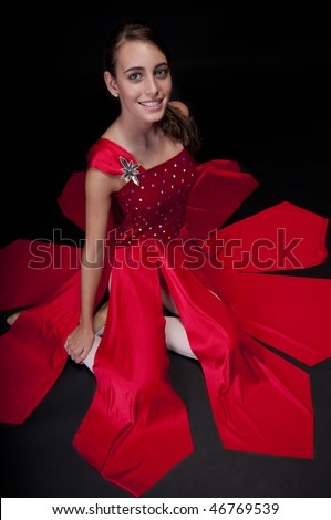 Young caucasian ballerina seated with long dress. Low key image.