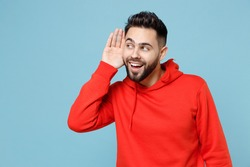 Young caucasian bearded curious attractive man 20s in casual red orange hoodie try to hear you overhear listening intently isolated on blue color background studio portrait People lifestyle concept