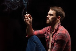 young caucasian bearded man in red checkered casual shirt sit smoking isolated over black background. man has dependency from smoking, hold cigarette in hand and look up at smoke