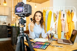 young caucasian blogger woman presenting new cosmetics in front of camera, woman show how she do every day make-up