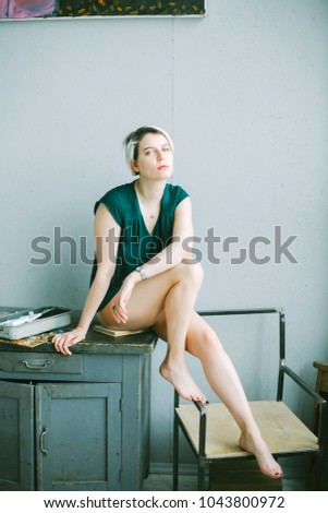Young Caucasian Blond Girl With A Short Haircut And Green Shirt With Naked Legs Indoor