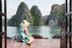 Young Caucasian blonde woman in a straw hat enjoying the boat ride at Lan Ha Bay, Cat Ba island, Vietnam