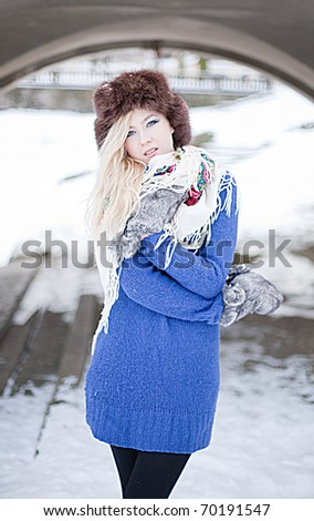 Young caucasian blonde woman wearing blue sweater, furry hat with gloves and traditional shawl in winter scenery.