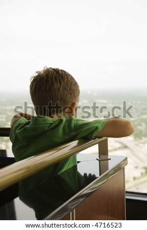 Young Caucasian boy leaning on railing at observation deck at Tower of the Americas in San Antonio, Texas.