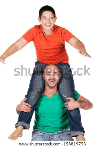Young caucasian boy wearing an orange t-shirt and blue jeans is playing with his father. The dad is wearing a green shirt. The boy is on the father's shoulders.