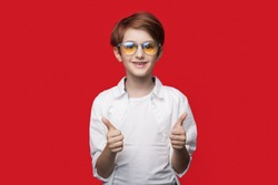 Young caucasian boy with glasses is gesturing the like sign on a red studio wall smiling at camera