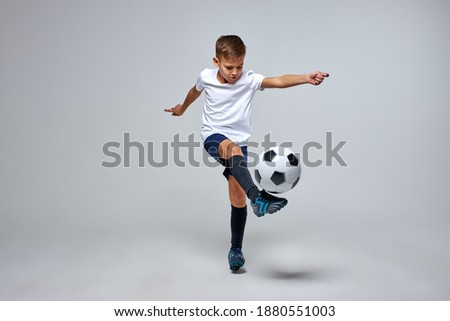young caucasian boy with soccer ball doing flying kick isolated in studio, athletic sportive boy in uniform