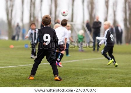 Young caucasian boys during a kids soccer training session on green turf.