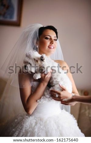 Young caucasian bride with a tiny dog.