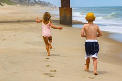 Young caucasian brother wearing a yellow hat chasing sister wearing a bathing suit on the beach