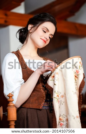Young Caucasian Brunette Woman Posing With Fancywork Hoop in Front of Spinning Wheel in Retro Dress In Rural Environment. Vertical Orientation Stock photo ©