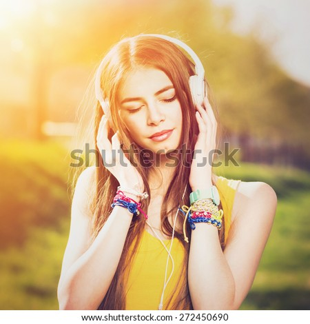 Young Caucasian brunette woman with headphones outdoors on sunny summer day. Millennial teenage girl listening to music wearing yellow shirt and vibrant jewelry. Square format, retouched, filter.