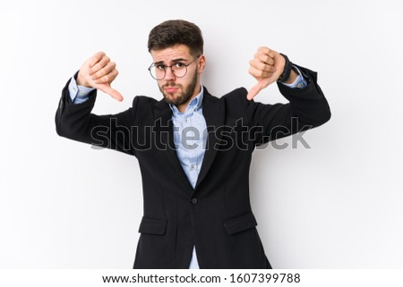 Young caucasian business man posing in a white background isolated Young caucasian business man showing thumb down and expressing dislike.