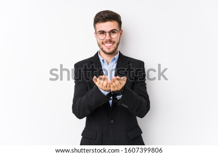 Young caucasian business man posing in a white background isolated Young caucasian business man holding something with palms, offering to camera.
