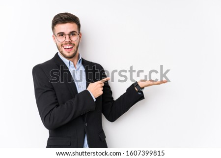 Young caucasian business man posing in a white background isolated Young caucasian business man excited holding a copy space on palm.