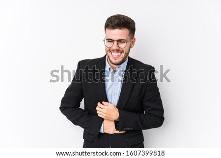 Young caucasian business man posing in a white background isolated Young caucasian business man laughs happily and has fun keeping hands on stomach.