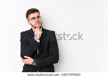 Young caucasian business man posing in a white background isolated Young caucasian business man looking sideways with doubtful and skeptical expression.