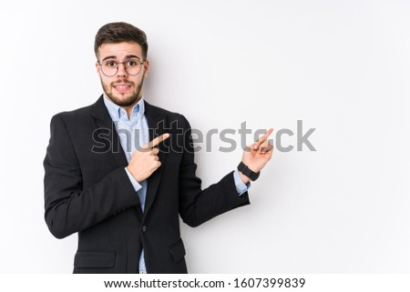 Young caucasian business man posing in a white background isolated Young caucasian business man shocked pointing with index fingers to a copy space.