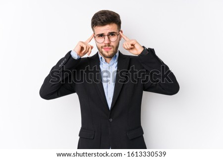 Young caucasian business man posing in a white background isolated Young caucasian business man focused on a task, keeping forefingers pointing head.