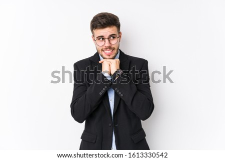 Young caucasian business man posing in a white background isolated Young caucasian business man keeps hands under chin, is looking happily aside.