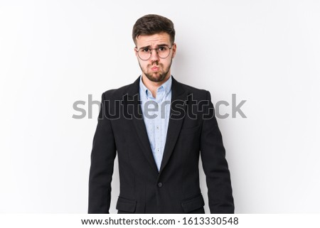 Young caucasian business man posing in a white background isolated Young caucasian business man blows cheeks, has tired expression. Facial expression concept.