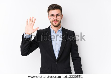 Young caucasian business man posing in a white background isolated Young caucasian business man smiling cheerful showing number five with fingers.