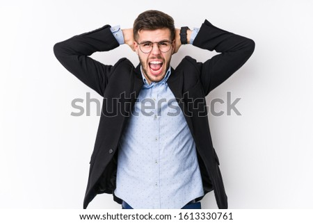 Young caucasian business man posing in a white background isolated Young caucasian business man covering ears with hands trying not to hear too loud sound.