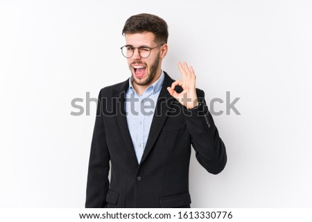 Young caucasian business man posing in a white background isolated Young caucasian business man winks an eye and holds an okay gesture with hand.