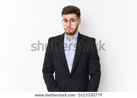 Young caucasian business man posing in a white background isolated Young caucasian business man shrugs shoulders and open eyes confused.