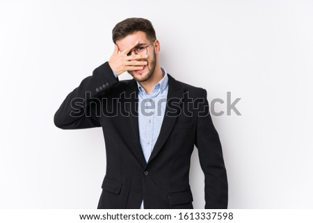 Young caucasian business man posing in a white background isolated Young caucasian business man blink at the camera through fingers, embarrassed covering face.