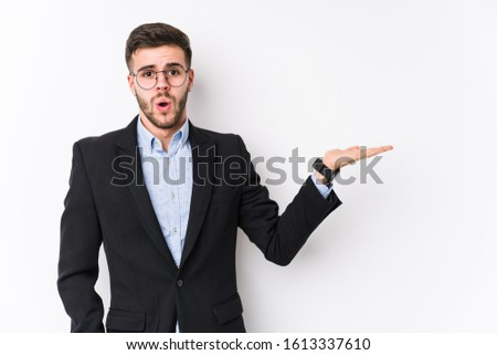 Young caucasian business man posing in a white background isolated Young caucasian business man impressed holding copy space on palm.