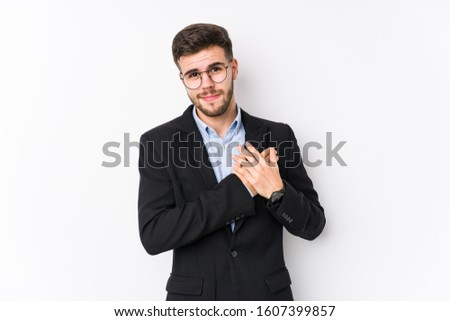 Young caucasian business man posing in a white background isolated Young caucasian business man has friendly expression, pressing palm to chest. Love concept.