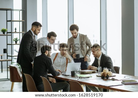 young caucasian business partners, handsome enthusiastic guys in tuxedo together in office. confdent and successful men sharing business ideas and opinions, speak about their market selling experience