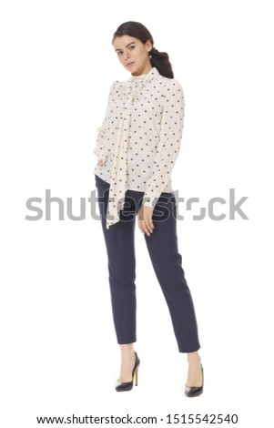 young caucasian business woman executive posing in formal polka dot official blouse with bow trousers high heels stiletto shoes full body isolated on white