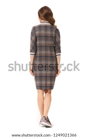 young caucasian business woman executive posing in official woolen checked dress sneakers shoes full body length isolated on white back view
