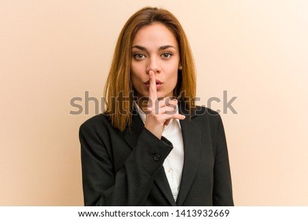 Young caucasian business woman keeping a secret or asking for silence.