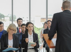 Young caucasian business woman looking to speaker, listening attentively with others and take note while he making a speech in corporate seminar event at conference room.