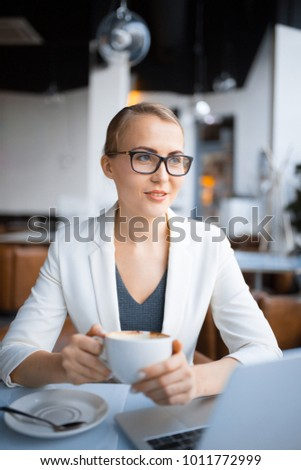 young caucasian business woman with glasses is sitting at a table with a drink in a cafe #1011772999