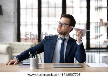 Young Caucasian businessman sit at desk in office have fun throw paper plane. Male boss or CEO entertain relax distracted from computer work at workplace. Business project, startup launch concept. ストックフォト ©