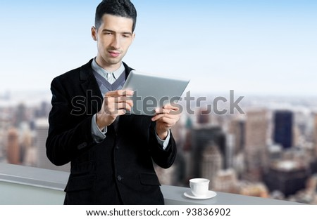 Young caucasian businessman with a cup of coffee uses a digital tablet on the roof of business center. Blurred cityscape with skyscrapers on background.