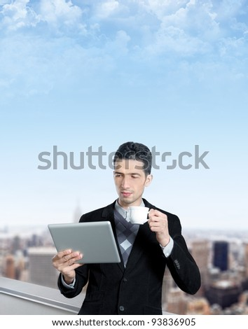 Young caucasian businessman with a cup of coffee uses a digital tablet on the roof of business center. Blurred cityscape with skyscrapers on background. Copy space added.