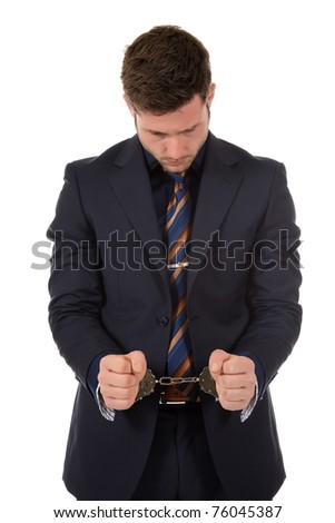 Young caucasian businessman with handcuffed hands . Studio shot. White background